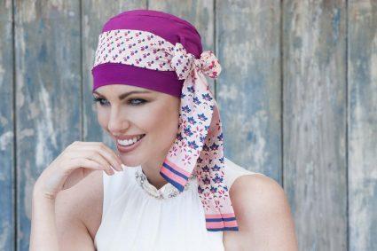 Beautiful chemo headscarf for women Yanna Purple Blush Florenza Woman wearing printed bow tie around purple cap