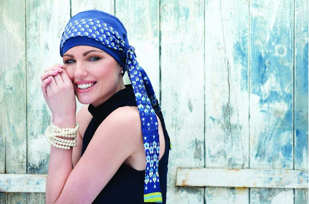Woman wearing blue Bamboo chemo scarf with printed scarf