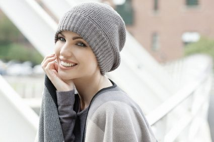 Woman wearing a soft grey knitted Basketweave Stitch chemo hat with soft fleece inside for extra comfort