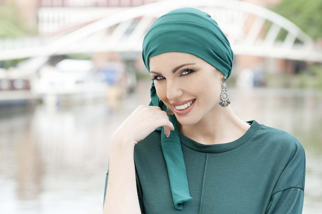 Woman wearing soft cotton chemo cap with long tail which could be shaped in many ways.