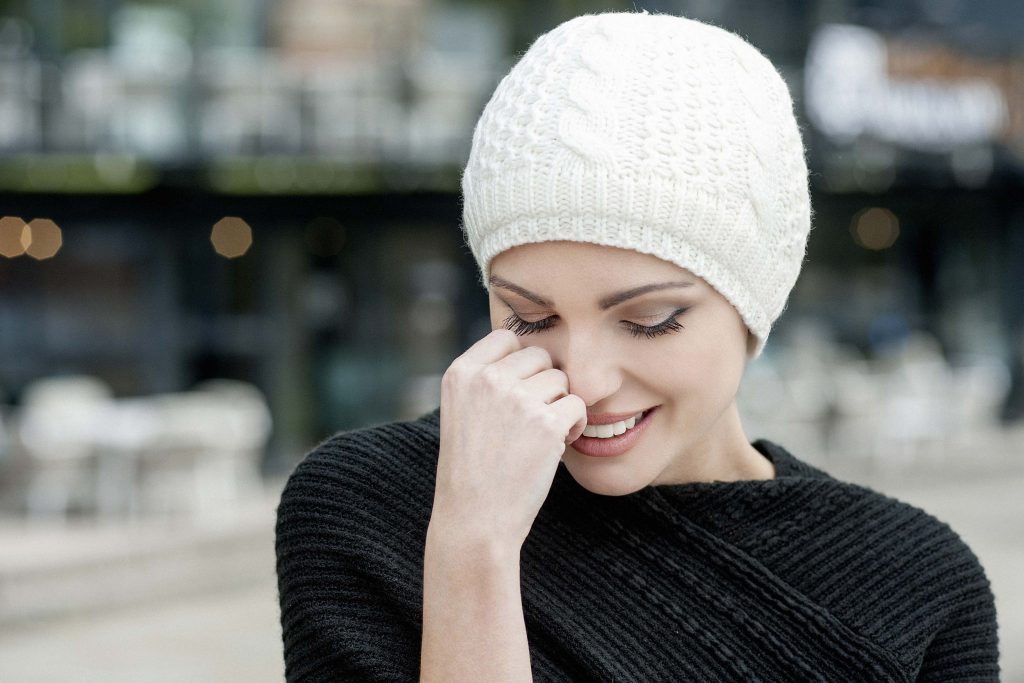 Winter hat for hair loss Bianca Woman wearing a soft white Single Rib Knit chemo hat with soft fleece inside for extra comfort