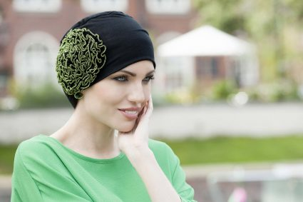 Cancer hats - Dahlia Woman wearing black soft bamboo chemo hat with beautiful big flower pattern with green thread