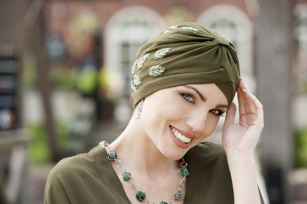 Woman wearing funky chemo headwear - green embellished soft cotton chemo headwear with golden and green embroidery in the shape of a leaf