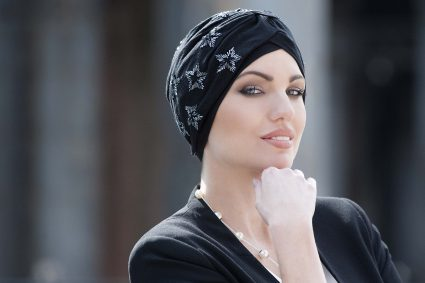 Hats for chemo patients - STAR BLACK BERYL Woman wearing black embellished soft cotton chemo headwear with silver embroidery in the shape of a star