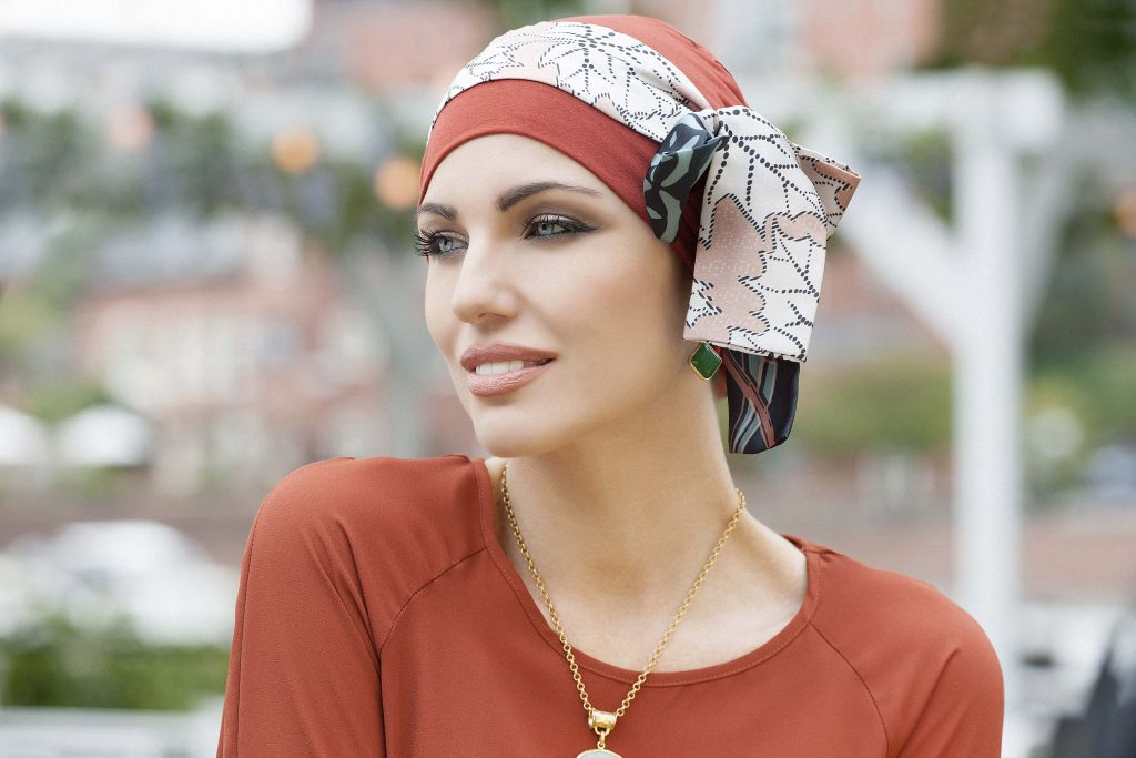 Turbans for hair loss Yanna Brick Sandy Foglia Woman in brick colour bamboo chemo hat with sandy leaf patterned scarf around the headwear