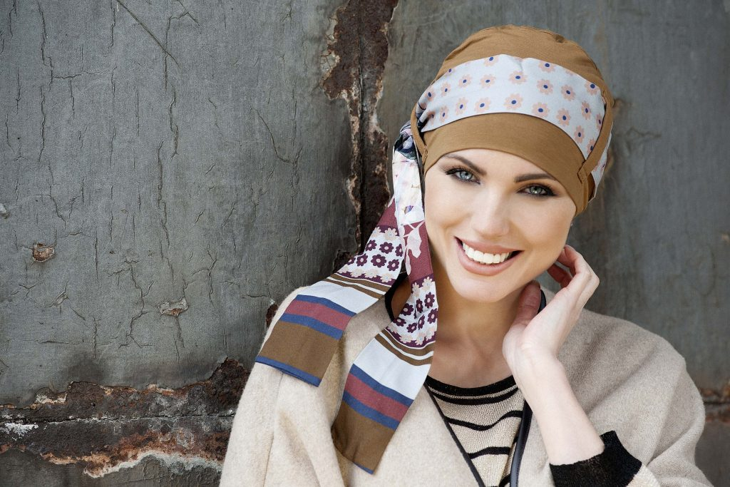 Bamboo Headwear for chemo patient Yanna Camel Sky Fiori Woman in camel color bamboo chemo hat with sky floral patterned scarf around the headwear