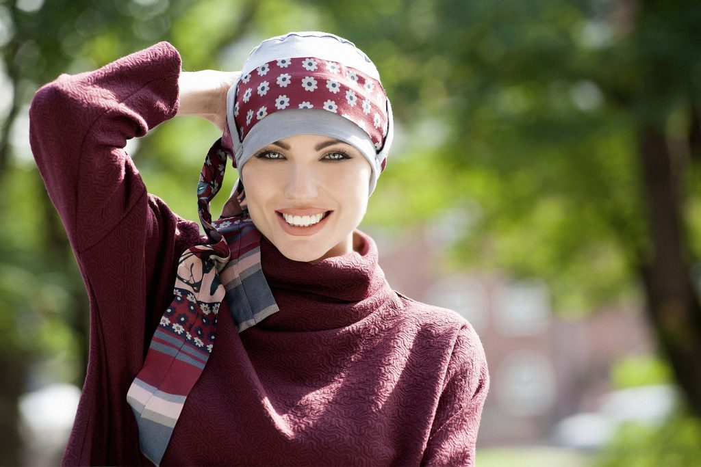 Headwear for cancer sufferers Yanna Grey Maroon Fiori Woman in grey colour bamboo chemo hat with maroon floral patterned scarf around the headwear