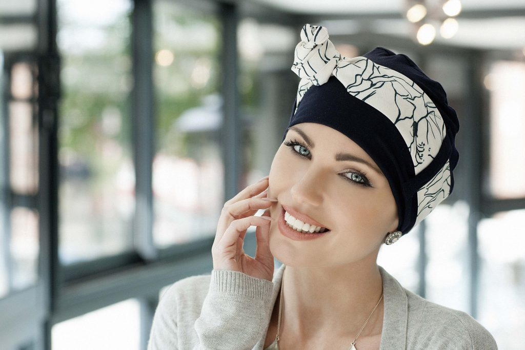Headscarves for cancer patients Yanna Navy White Lilium Woman in a navy color bamboo hat with a white patterned scarf around the headwear
