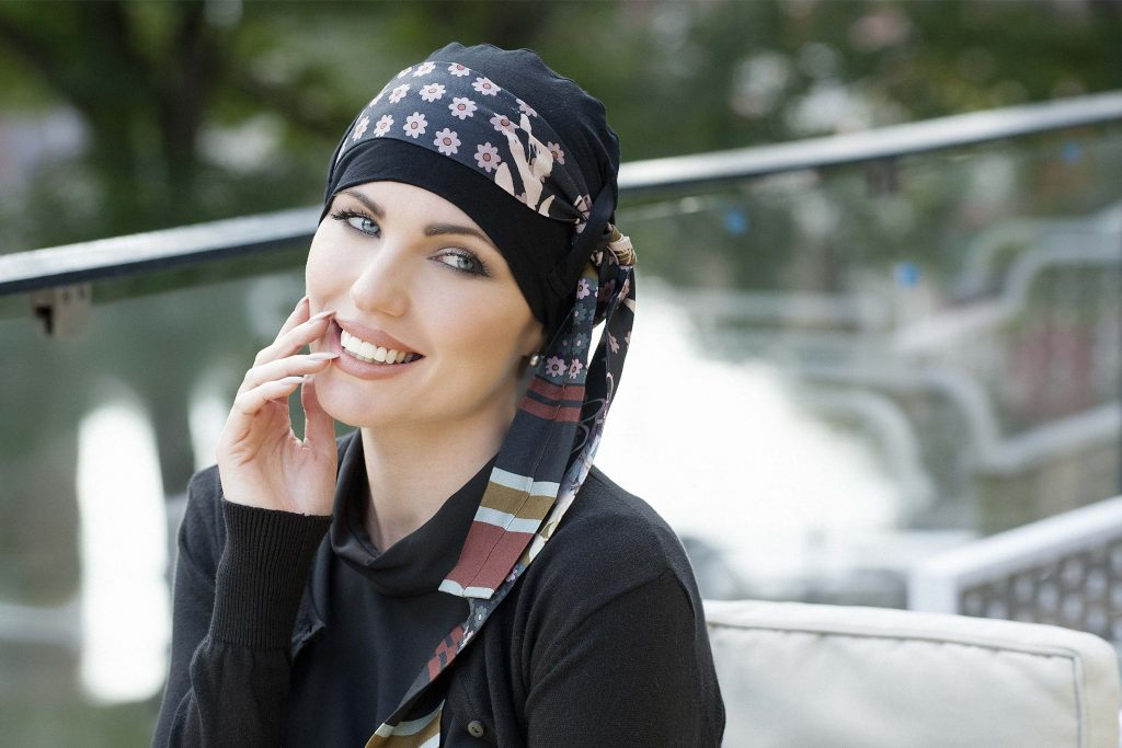 Bamboo hats for cancer patients UK Yanna Black Blush Fiori Woman in black colour bamboo chemo hat with blush floral patterned scarf around the head