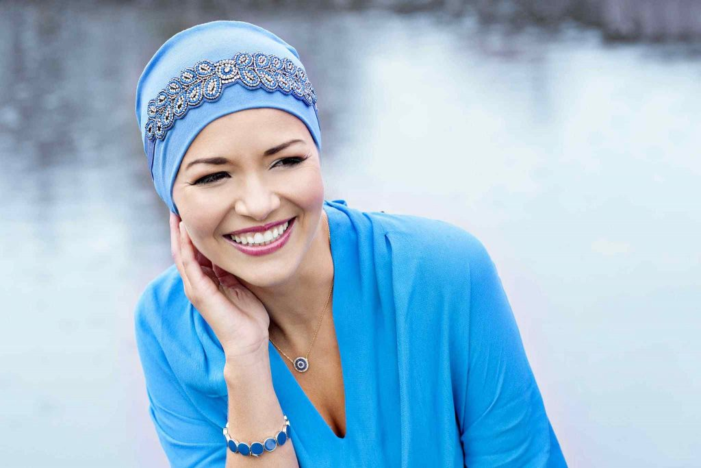 woman wearing jewelled light blue chemo cap
