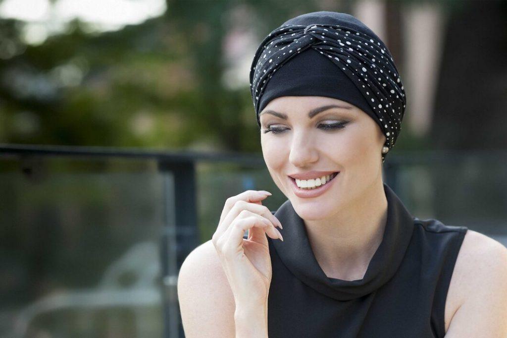 woman wearing black chemo hat with white polka dot