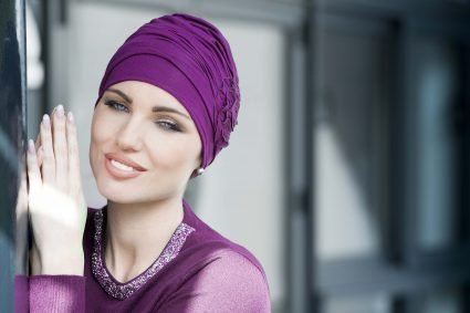 A woman weaat with a flower chemo hatring purple h