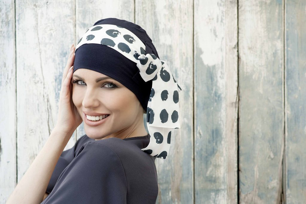 A woman wearing a Bamboo hats for cancer patients women - Yanna Navy Polka Dot