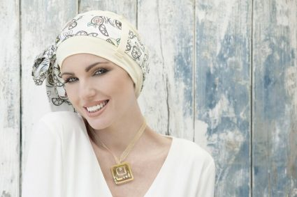 A woman is wearing bamboo hat and a scarf with lemon pattern Yanna Yellow Lemon- chemotherapy headwear for chemo