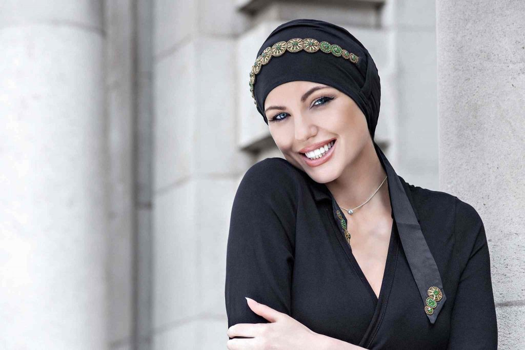 woman wearing black chemo cap with golden flower crown