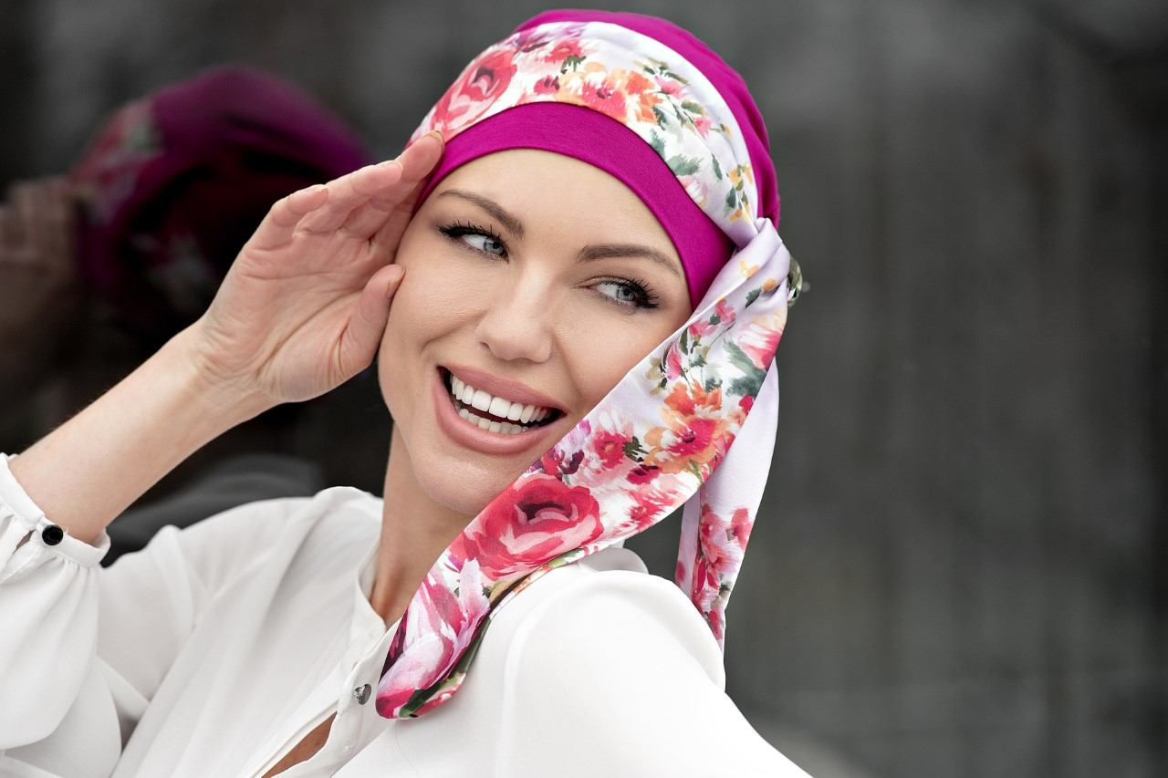 Woman wearing purple chemo cap with floral wrap
