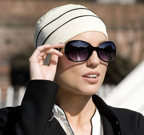 woman with sunglasses wearing chemo cap with black stripes